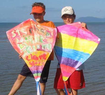 2 boys showing off their finished design after kite making lesson