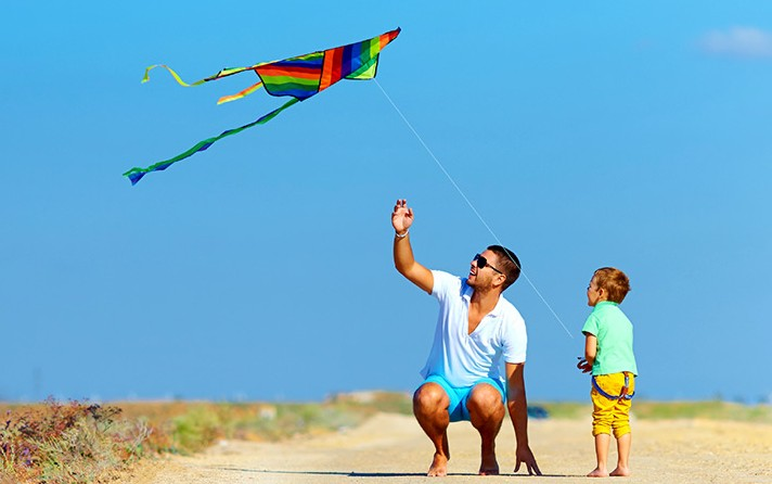 dad and son flying a delta kite
