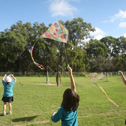 Boy launching the single string kite he made in class kite making workshop