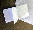 applying sticky tabs to corner of kite making kite sail