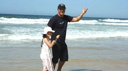 dad and daughter flying the kite they made at a kite making workshop